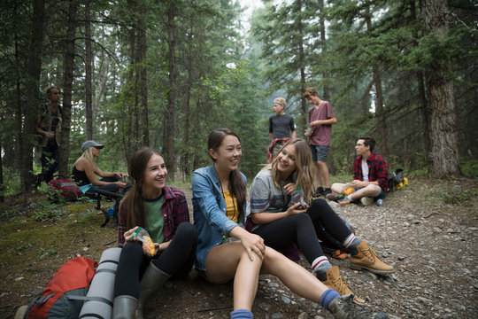 Smiling teenage girl outdoor school students hiking, resting in woods