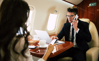 Preparing for presentation. Close-up photo of attractive man in a suit, who is talking on the phone, while typing something on his laptop, sitting near his colleague in the window seat in aircraft