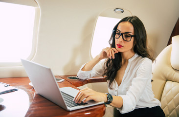 A nice businesswoman in formal attire and glasses, who is typing something on her laptop with...