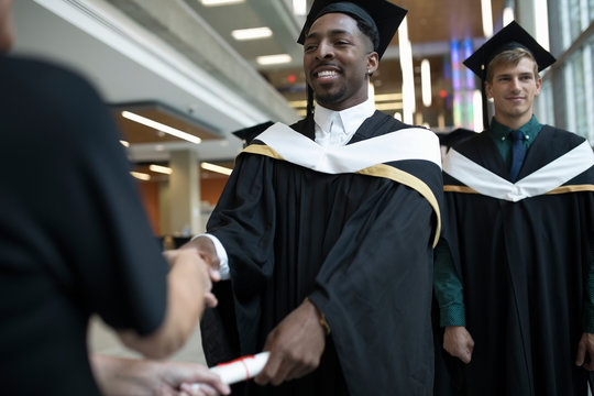 College student graduate in cap and gown receiving diploma at ceremony