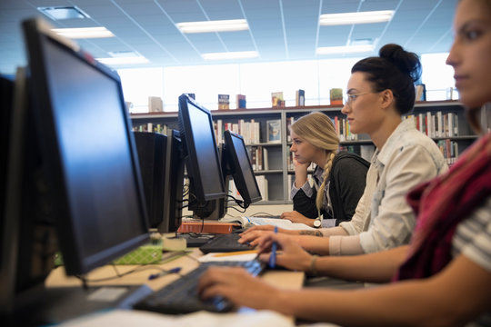 Smiling female college students researching at computers in library