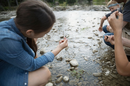 Curious teenage girl outdoor school student collecting water sample in stream