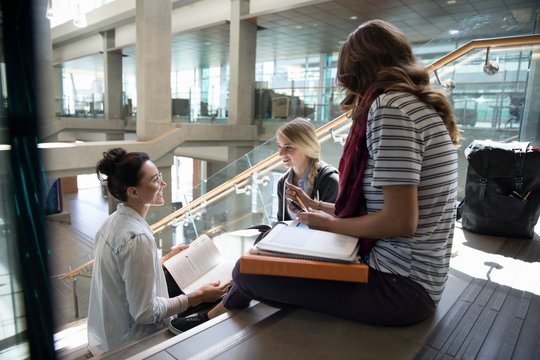 Female college students studying, talking on stairs