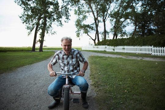 Playful senior man riding tricycle on rural path