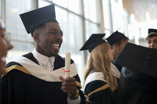 Enthusiastic, confident male college student graduate in cap and gown holding diploma