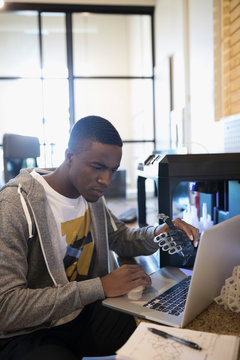 Focused male designer with prototype working at laptop, using 3D printer in office