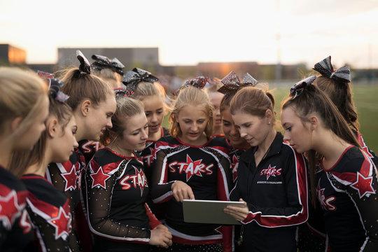Teenage girl high school cheerleading team using digital tablet