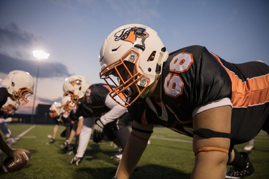 Teenage boy high school football player lineman playing on football field