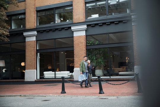 Senior couple walking on urban sidewalk past storefronts