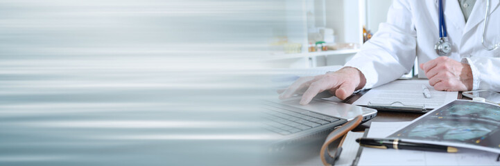 Doctor using a laptop; panoramic banner