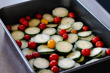slices of zucchini and cherry tomatoes in oven tray ready to get cookied