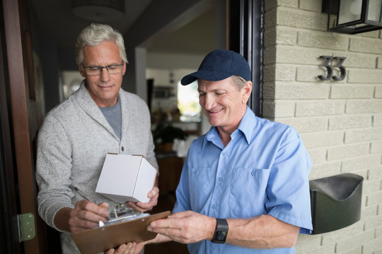Senior man signing clipboard for box package for delivery man at front door