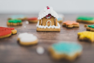 festive gingerbread house and cookies in different colors and shapes