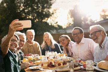 Smiling senior friends posing for selfie at garden party lunch at sunny patio table