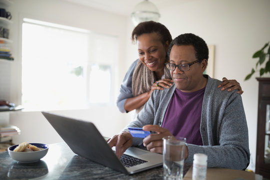 Smiling senior couple with credit card paying bills online at laptop in kitchen