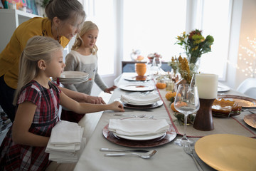 Grandmother and granddaughters setting the table for Thanksgiving dinner
