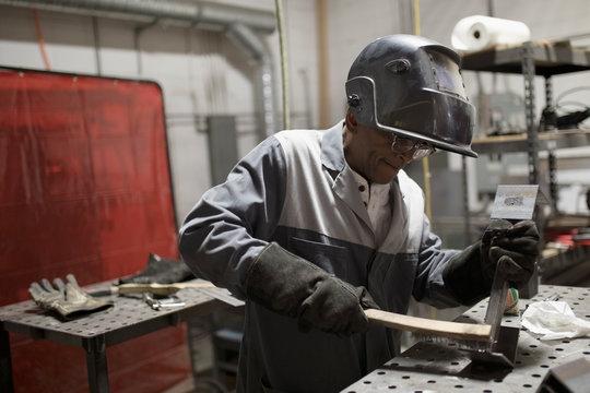Welder in welding mask working at workbench