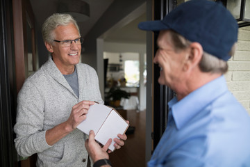 Smiling senior man receiving box package from delivery man at front door
