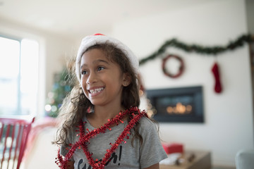 Smiling girl in Christmas Santa hat wrapped in red garland, looking away