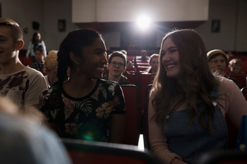 Smiling tween girl friends watching movie in dark movie theater