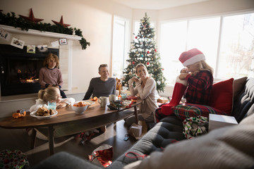 Curious girl opening Christmas stocking with family in living room