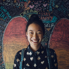 Portrait smiling, confident Asian tween girl against wall with chalk wings