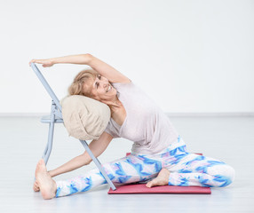 Senior woman doing yoga with chair at home. Stretching exercises
