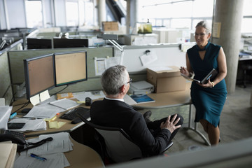 Businessman and businesswoman talking, meeting in office cubicle