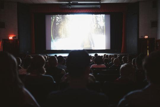 People watching movie in dark movie theater