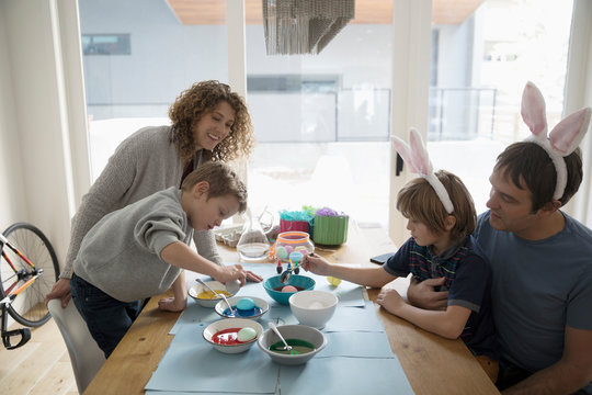 Family in costume rabbit ears dyeing Easter eggs at table