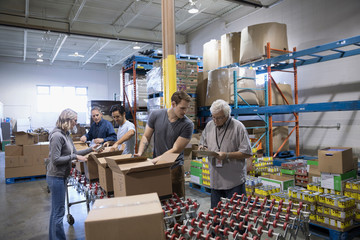 Volunteers boxing canned Food for Food drive in warehouse