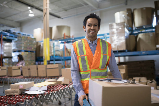 Portrait smiling, confident male warehouse manager with cardboard box in shipping warehouse