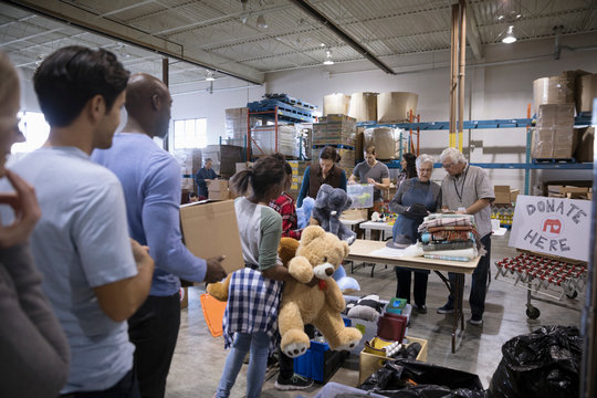 Volunteers taking clothing and toy donations in warehouse