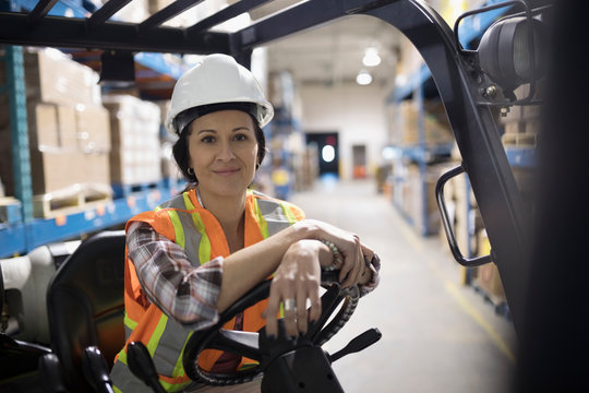 Portrait smiling, confident female worker driving forklift in distribution warehouse