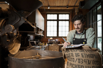 Male coffee roaster with clipboard roasting coffee