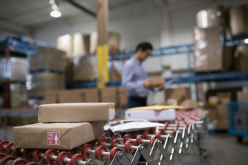 Male warehouse manager checking packages on production line conveyor belt