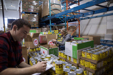 Male volunteer taking canned Food drive inventory in warehouse