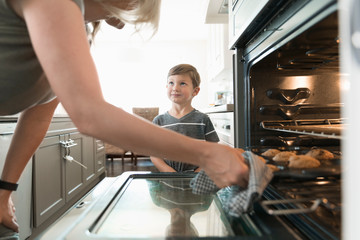 Mother and son baking muffins, taking them out of the oven in kitchen