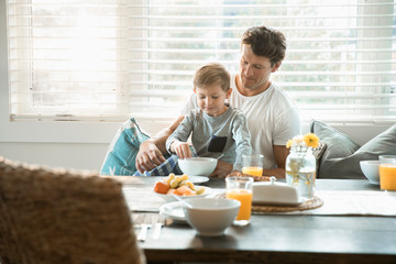 Father and son eating breakfast in breakfast nook