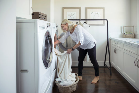 Woman removing laundry from dryer in laundry room