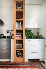 Narrow bookshelf with cookbooks in kitchen