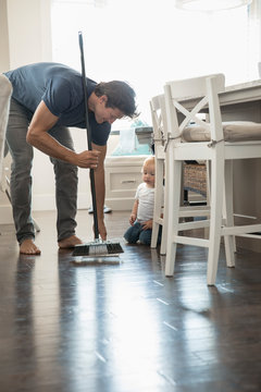 Baby son watching father sweeping floor