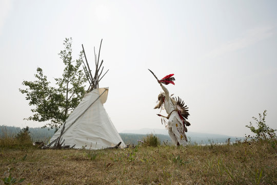 Native American Indian dancing in traditional clothing outside teepee