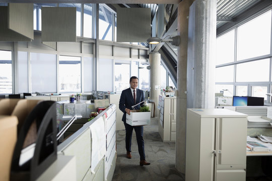 Businessman being laid off, carrying box of belongings in office