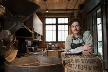 Portrait confident male coffee roaster roasting coffee
