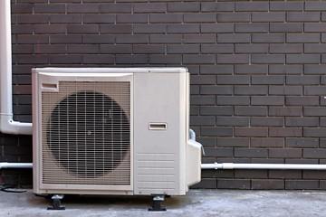 Air conditioner compressor install on concrete floor next to vintage dark brown brick wall behind...