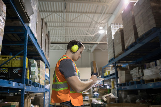Male worker with clipboard and ear protectors checking inventory in distribution warehouse