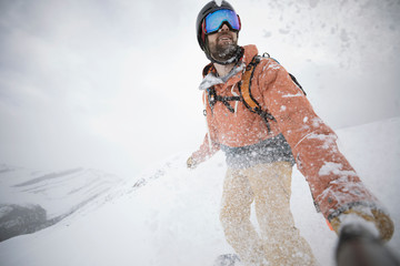 Male snowboarder snowboarding with wearable camera on monopod in snow