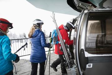 Family skiers getting into gondola at ski resort