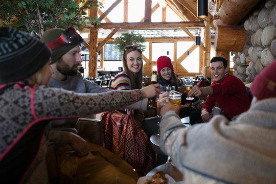 Friends enjoying apres-ski, toasting beers in ski resort lodge